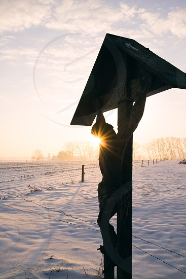 Rural landscape snow covered fields ethereal light sunrise Christ statue religion superstition. photo