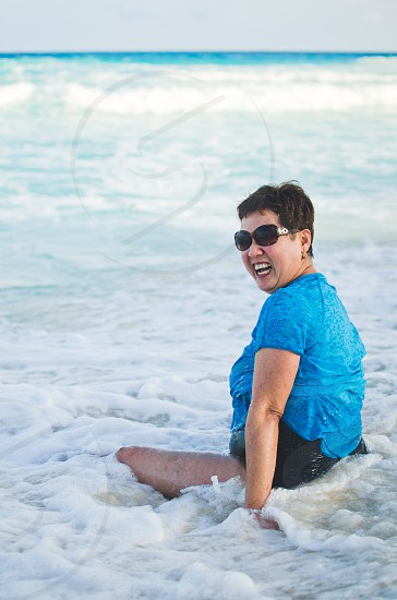 Older woman laughing and smiling while sitting in the ocean waves. photo