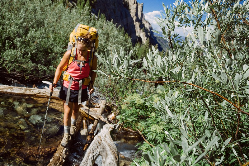 A woman making a creek crossing while backpacking through the Sawtooth Wilderness in Idaho photo