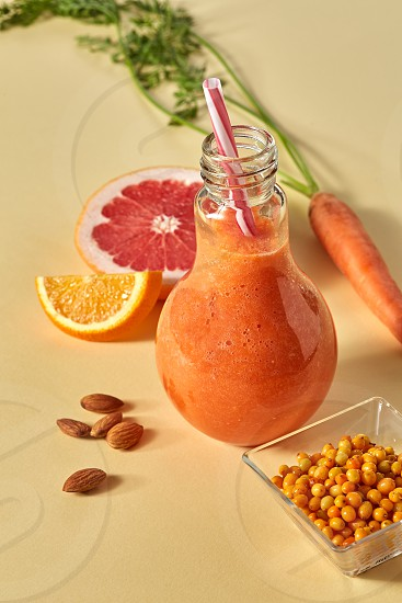 Vitamin drink with carrots sea buckthorn grapefruit and orange in a glass with a straw on an orange paper background. Healthy Eating photo