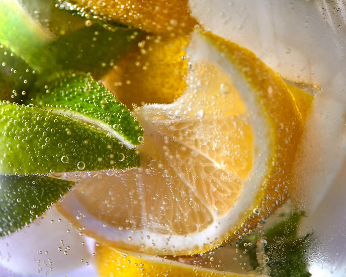 Slices of lemon and lime with bubbles of water in a glass. Macro photo of refreshing lemonade photo