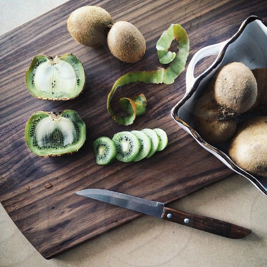 green and brown round shaped fruits on brown wooden chopping board photo