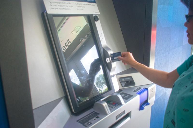 Woman making a bank transaction using an ATM machine photo