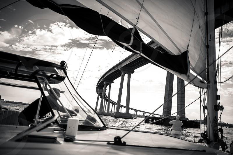 A sailboat / ship / vessel travels under the Coronado Bay Bridge in San Diego as the skipper navigates the seas. photo
