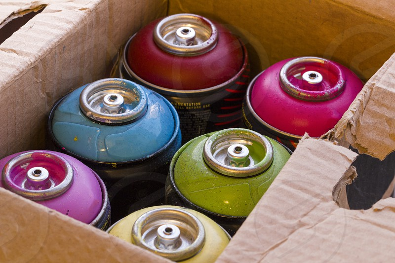 Box full of colored spray cans. photo