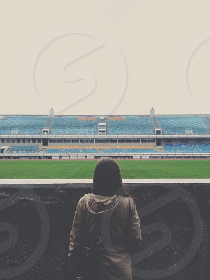 Girl looking at an empty stadium photo