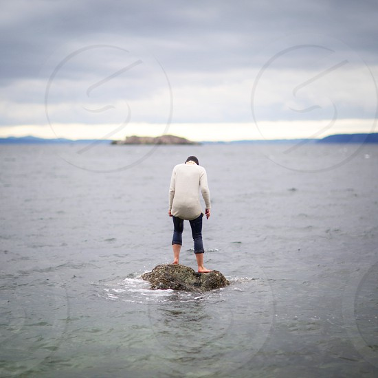person in white long sleeve shirt and blue capri pants standing on brown rock in sea water under blue white smooth clouds photo