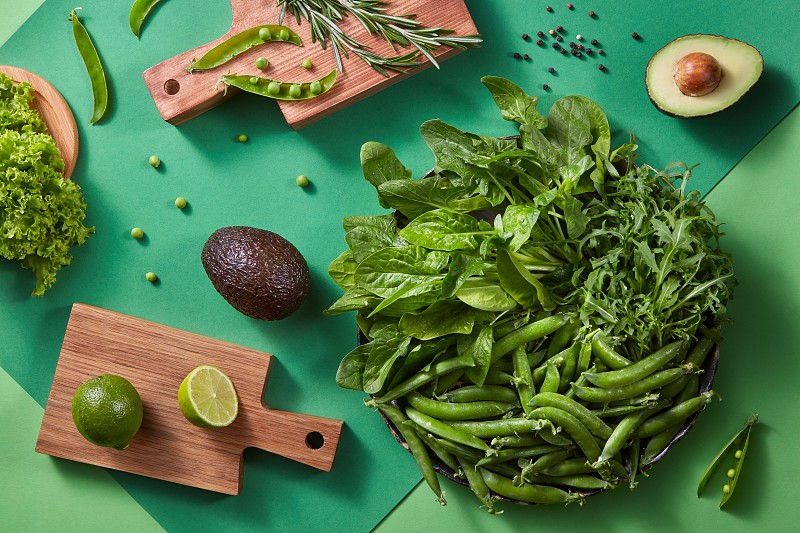 Top view of the natural organic fresh green vegetables on a duotone green background for cooking a vegetarian salad. Healthy lifestyle. Vegetarian organic food. photo