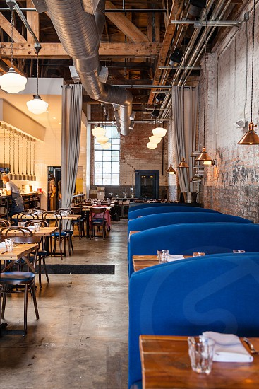 blue padded couch and brown wooden tables inside gray cement wall restaurant photo
