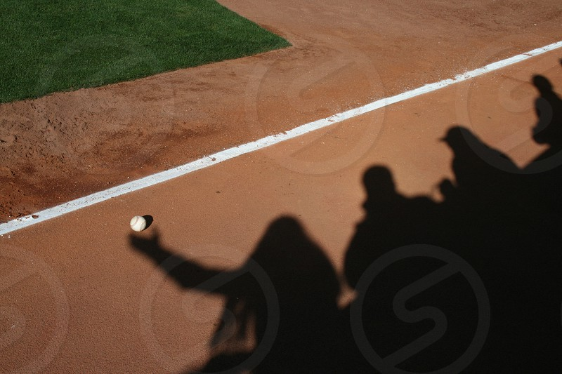 Baseball fans catching a ball shadows photo