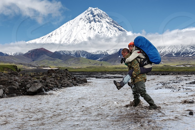 KAMCHATKA PENINSULA RUSSIAN FAR EAST - JUNE 30 2014: Guide helps young women tourist to cross muddy rugged mountain river - strong man carries woman on her back on background beautiful volcano cone. photo