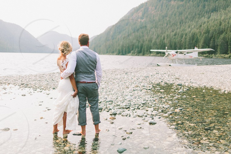 A bride and groom looking at their seaplane from a river. photo