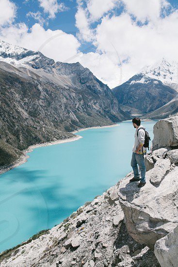 Young man standing on the edge of a cliff in Paron Lake Huaraz Perú. photo