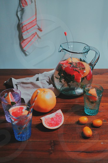 Grapefruit and mint drinks and a pitcher on a wooden table photo