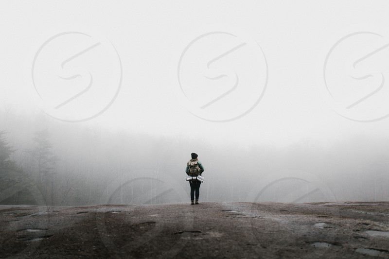 A female hiker stands on the edge of a cliff with her backpack in winter staring off into the fog and forest below photo