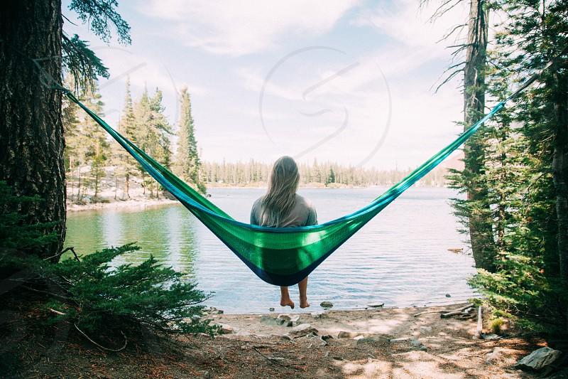 woman sitting on green hammock near green trees during daytime photo