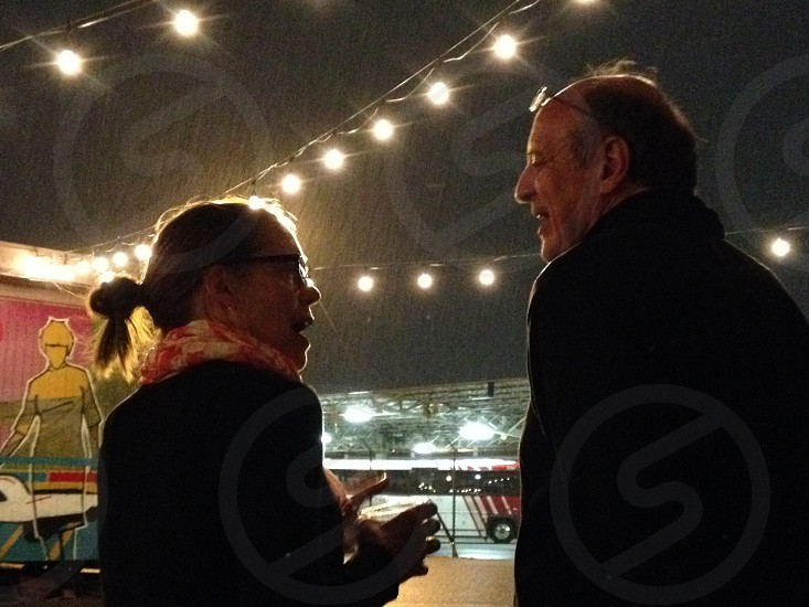 woman and man talking under stringed lights photo