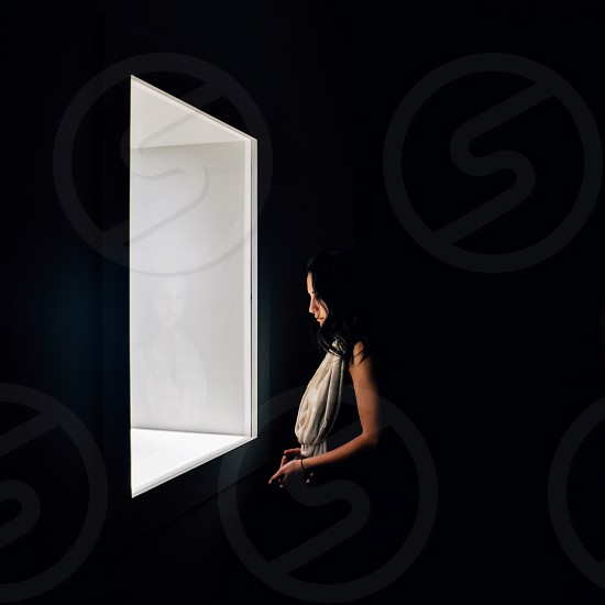 woman beside window photo