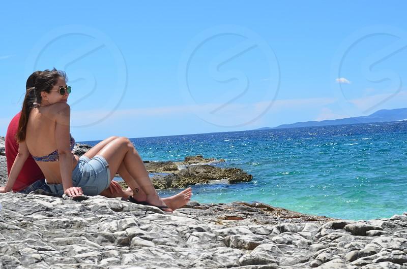 man and woman sitting on rocks near body of water photo