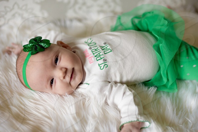 Baby newborn girl Irish smiling laying down green St. Patrick's Day St. Paddy's Day baby's first adorable heritage generations tutu shamrock clover headband looking at camera happy child one person white fur photo