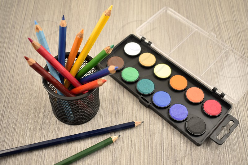 Watercolor tool. Back to school border. Art supplies on a wooden background. School supplies for painting photo