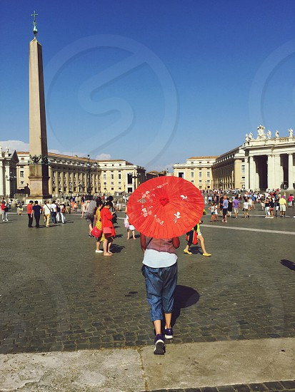 St Peters square Rome girl umbrellaparasoll summer blue sky tourists photo