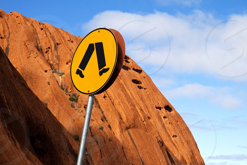 Stark image of a pedestrian crossing sign against the face of iconic Uluru with blue sky and fluffy white clouds. photo