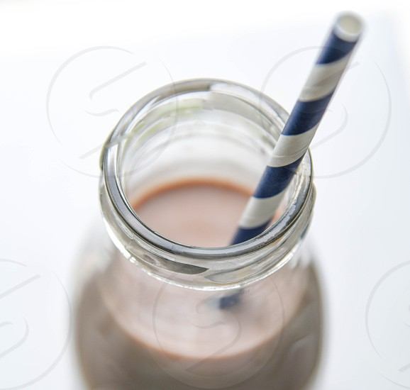 white and blue striped plastic straw in clear glass bottle photo