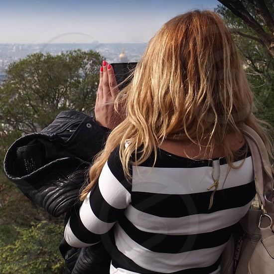 cell phone girl taking picture blond fingernails trees photo