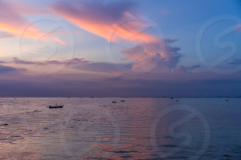 Small boats on a vast ocean after sunset. photo