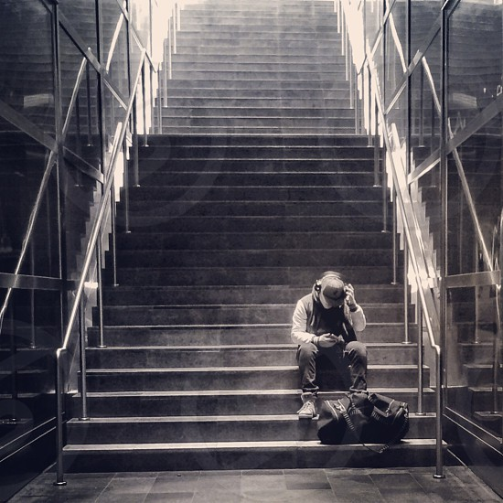 man holding hat seated at the foot of concrete stairs photo