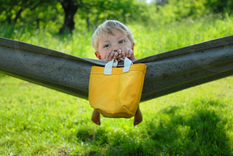 little boy boy green yellow bag hammock summer toy bag grass  photo