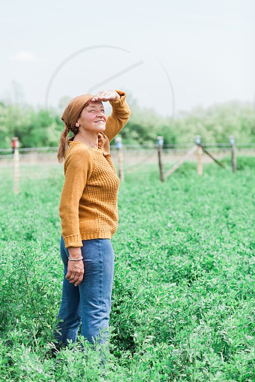 Mature woman in the field looking into the sky photo