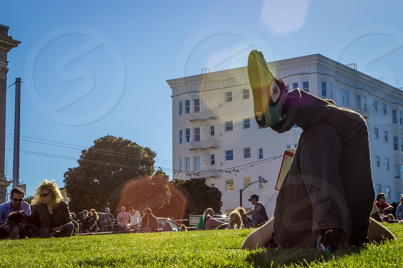 guy reading a book at Alamo Square in San Francisco. Sunny day people at the park.  photo