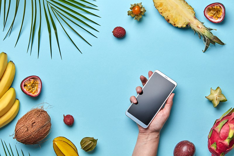 Palm leaf coconut lychee pineapple set of tropical fruits. The girl's hand is holding the phone on a blue background with a copy of the space. The concept of modern online shopping. Flat lay photo