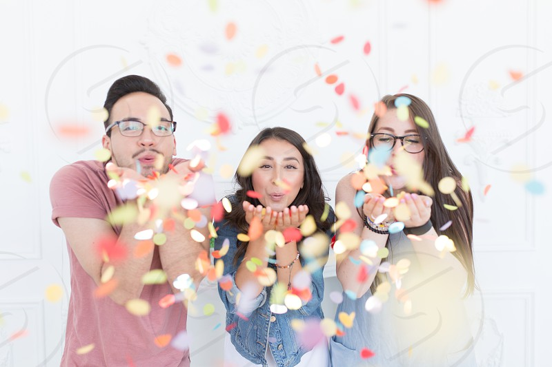 A group of diverse millennials celebrating by blowing confetti photo