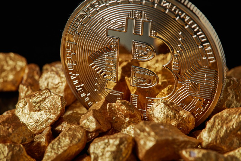 Closeup of Gold Bitcoin Coin and gold nugget on black background. Concept of financing Bitcoin cryptocurrency in Noble metal photo