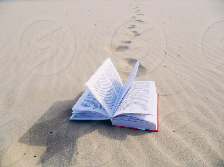 book in sand with trail of footprints photo