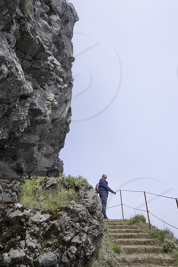 woman walking on the track at the pic arieiro one of the highest mountains of madeira island photo