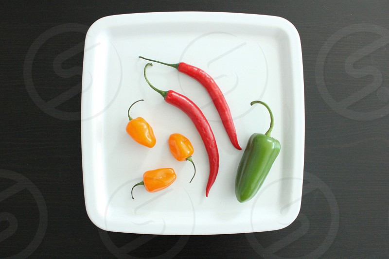 white square plate chili pepper jelapenio and yellow pepper photo
