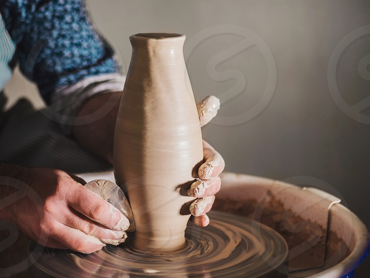 Creating earthenware and traditional pottery concept. Experienced male potter's hands creating beautiful clay product - vase - using professional tools. photo