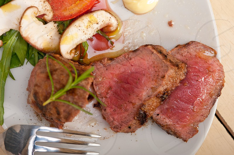 beef filet mignon grilled with fresh vegetables on side mushrooms tomato and arugula salad photo