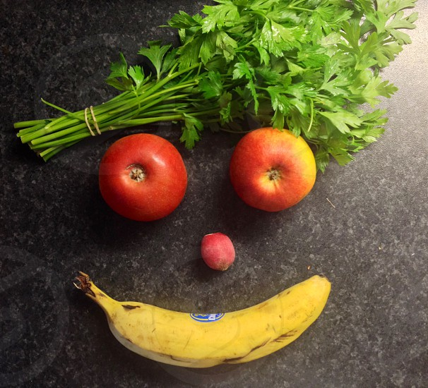 parsley two apples peach and banana fruits on gray granite surface photo