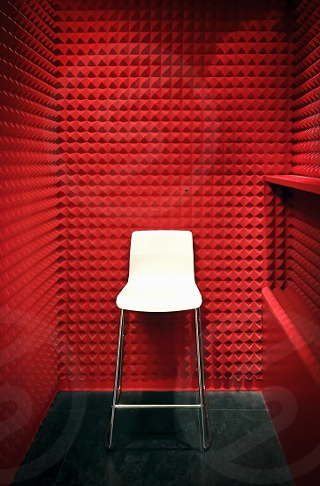 white chair on a red soundproofed cabin photo