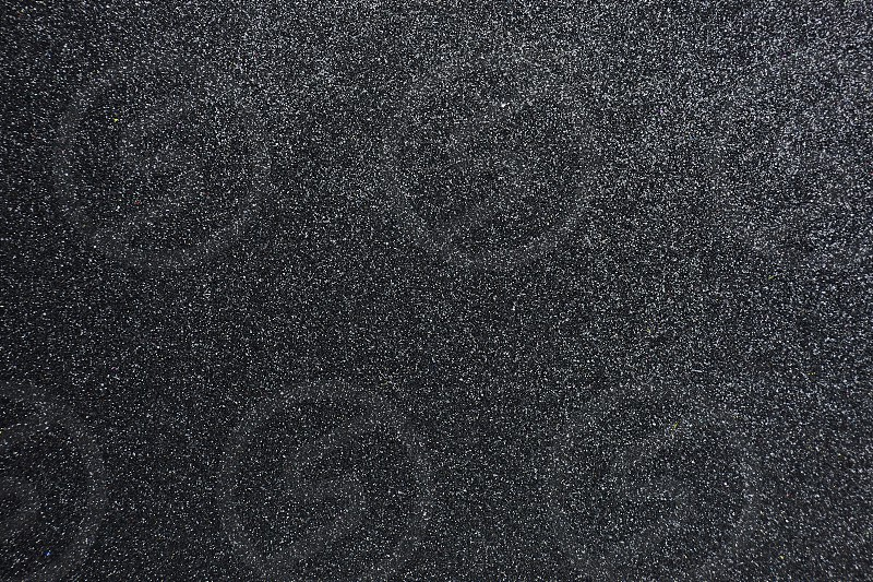Bumpy black glitter textured abstract background for presentation backdrop wallpaper Closeup photo