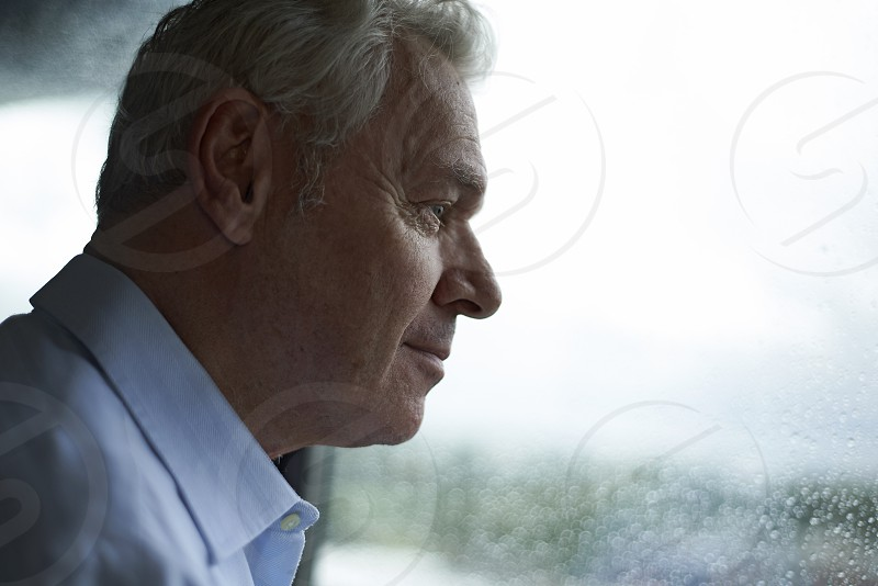 Elderly man looking out of a rainy window looking for someone waiting for someone photo
