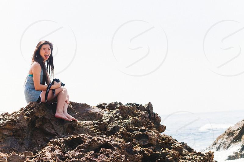 woman sittin on rock smiling photo