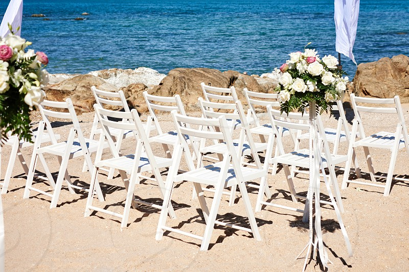 White wedding chairs line up on the sand at the wedding ceremony decoration with roses flower photo
