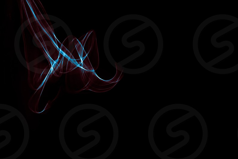 Light painted glowing abstract blue and red curved lines on a black background photo
