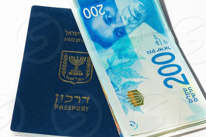 Stack of israeli money bills of 200 shekel and israeli passport - Top view. photo
